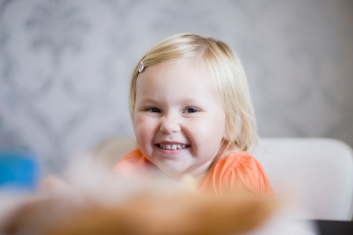 Toddler girl smiling at dinner table